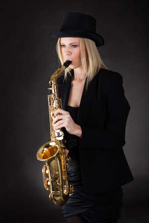 Beautiful young woman playing saxophone over black background photo
