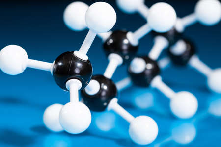reaction: Model of molecular structure on blue reflective background Stock Photo