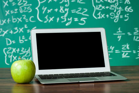 educational tools: Laptop and apple on the desk in front of blackboard