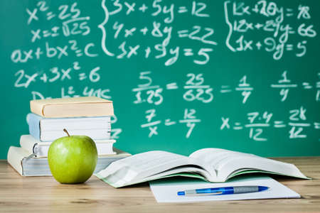 equation: School textbooks on a desk in front of blackboard