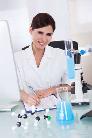 Happy Female Scientist In Laboratory Writing On Notepad photo