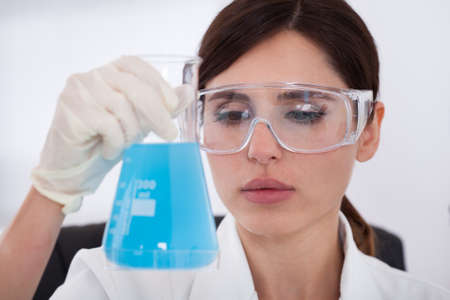 Female Scientist Looking At Chemical In Flask photo