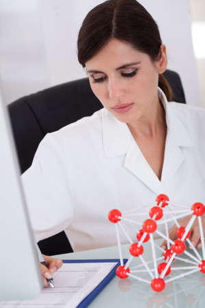 Female Scientist Sitting In Laboratory And Writing On Clipboard Stock Photo - 18336537