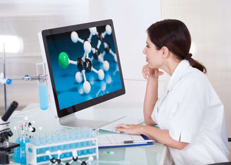 Female Scientist Looking On Computer Screen In Lab photo