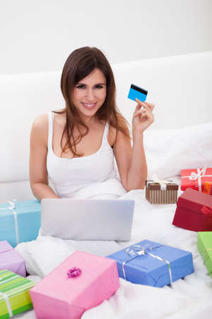 Young Woman Sitting On Bed And Shopping Online Stock Photo - 18336535