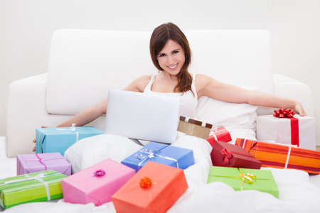 Young Woman Sitting On Bed And Shopping Online Stock Photo - 18336495