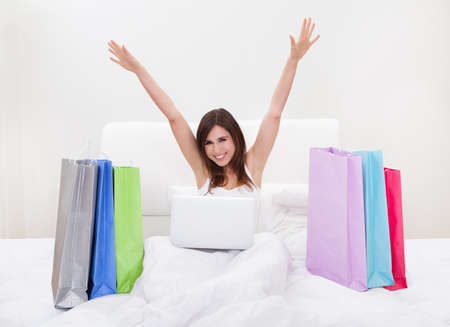 online shopping: Young Woman Sitting On Bed And Shopping Online Stock Photo