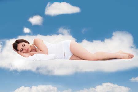 Gyönyörű fiatal nő alszik felhők az égen
