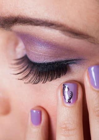 parpados: Primer plano de los ojos de la mujer con p�rpura sombra de ojos y el dedo Esmalte de U�as Foto de archivo