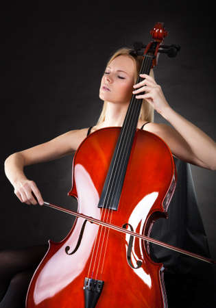 playing folk: Beautiful young woman playing cello over black background