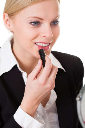 Attractive businesswoman applying lipstick. Isolated on white photo