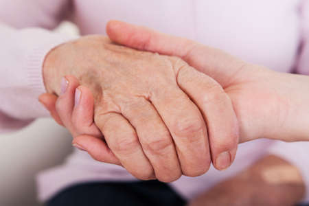 Young Woman Holding Senior Woman's Hand; Indoor Stock Photo - 18461904