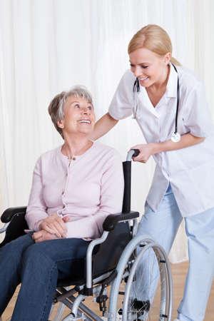 Zorg Doctor helpen van gehandicapte Senior Patiënt Binnen