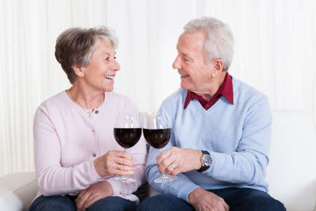 Senior Couple Toasting Glass Of Wine; Indoor photo