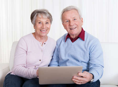 Senior Couple Sitting On Couch And Looking At Laptop Computer photo