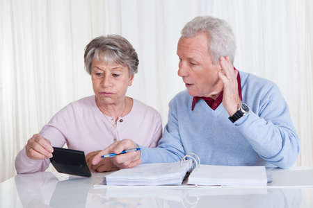 concerned: Stressed Senior Couple Calculating Budget At Home