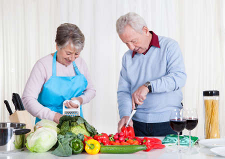 cutting vegetables: Happy Senior Couple Cutting Vegetables In Kitchen