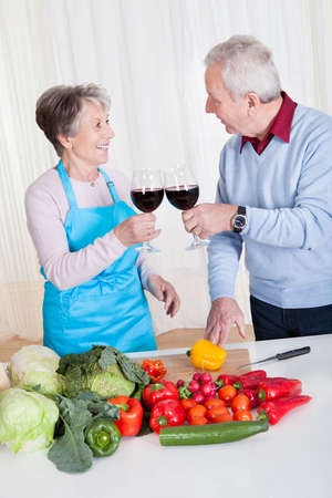 Senior Couple Toasting Wine While Cutting Vegetable In Kitchen photo