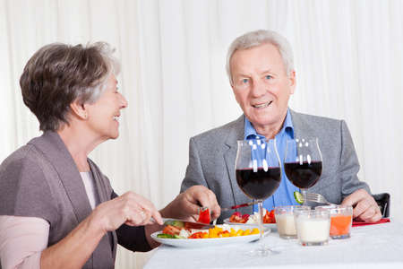 lifestyle dining: Portrait Of Senior Couple With Wine Glasses Sitting At A Restaurant Stock Photo