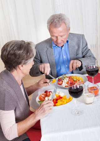 Portrait Of Senior Couple With Wine Glasses Sitting At A Restaurant photo