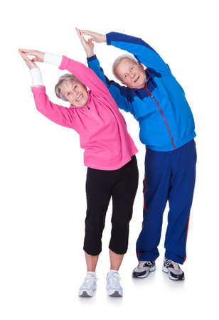 old people smiling: Portrait Of A Senior Couple Exercising On White Background