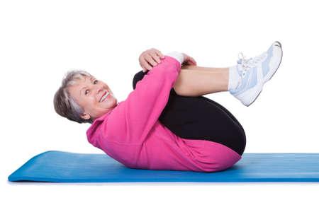 bend: Portrait Of Senior Woman Exercising On White Background