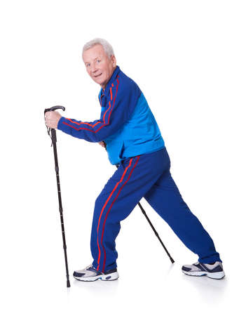 trekking pole: Senior Man Walking With Hiking Poles On White Backgrounds Stock Photo