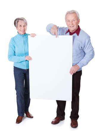 Happy Senior Couple Holding Blank Placard On White Background photo