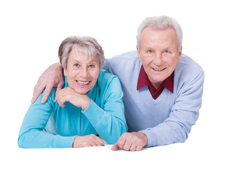Portrait Of Happy Senior Couple Lying Over White Background Stock Photo - 18497271