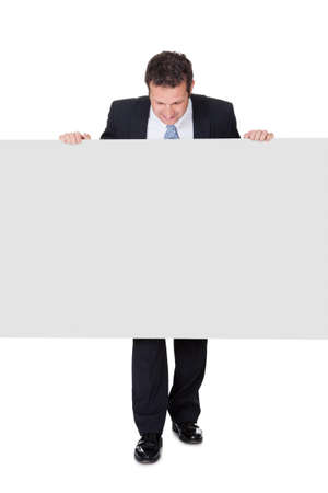 Successful businessman presenting empty banner. Isolated on white background photo