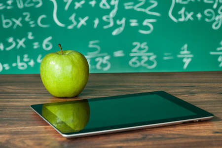 classroom: Digital tablet and apple on the desk in front of blackboard