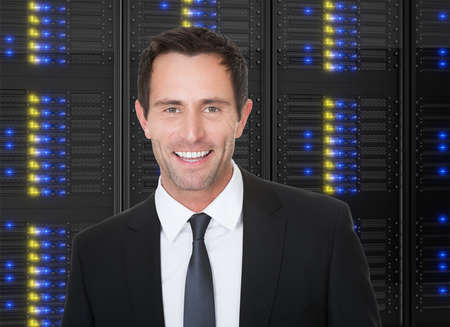 Photos of businessman standing in front of server racks photo