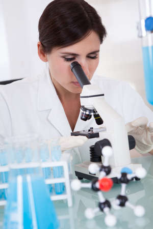 lab tech: Female Scientist In Laboratory Looking Through Microscope Stock Photo