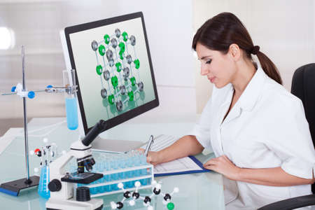 Female Scientist Sitting In Laboratory And Writing On Clipboard photo