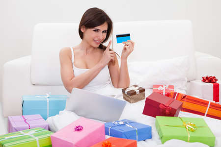 e pretty: Young Woman Sitting On Bed And Shopping Online Stock Photo