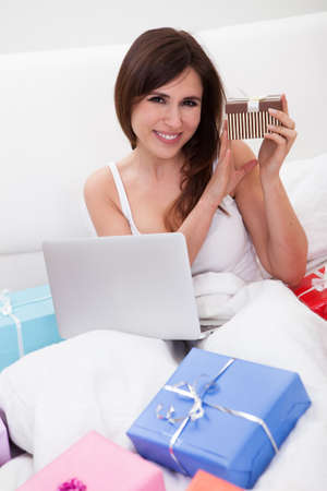 Young Woman Sitting On Bed And Shopping Online Stock Photo - 18497228