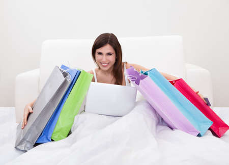 Young Woman Sitting On Bed And Shopping Online Stock Photo - 18497214