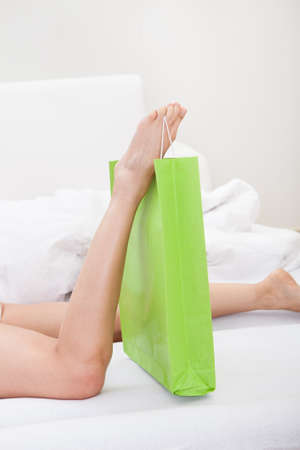 Close-up Of Woman's Leg Holding Shoppingbag On Bed Stock Photo - 18461894
