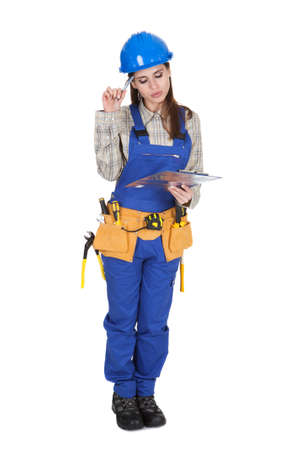 protective workwear: Portrait Of Young Female Worker Writing On Clipboard