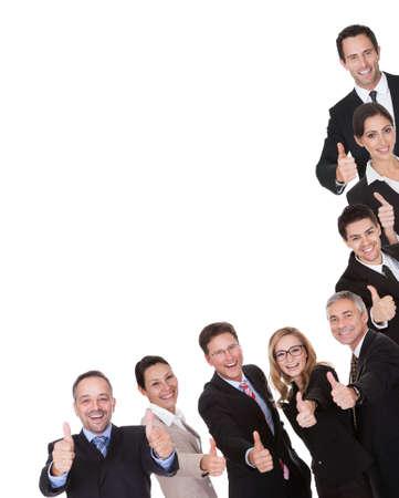 Gruppo di dirigenti aziendali con un pollice alzato di approvazione e la vittoria Ridendo come celebrano un esito positivo isolato su bianco Archivio Fotografico