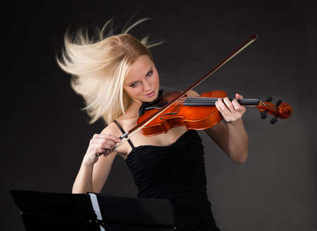 Young woman passionately playing violin over black background photo