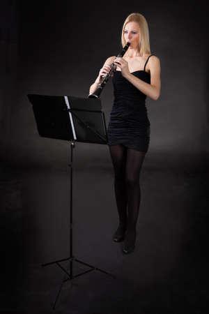 clarinete: Joven y bella mujer tocando el clarinete sobre fondo negro