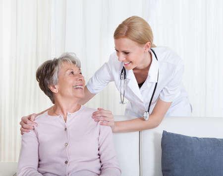 enfermeria: Retrato de joven m�dico y paciente mayor que se sienta en el sof�