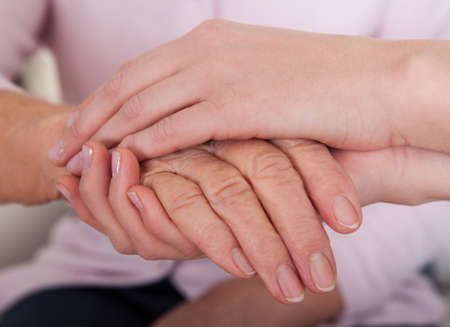 assisting: Young Woman Holding Senior Womans Hand; Indoor