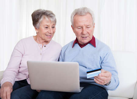 Senior Couple Sitting On Couch And Shopping Online With Laptop Computer photo