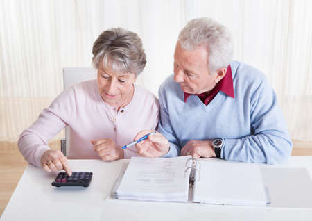 retirement: Photo of Senior Couple Calculating Budget At Home