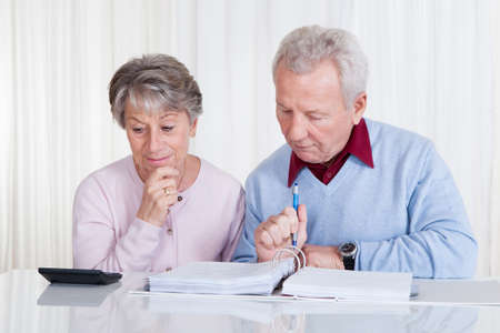 Stressed Senior Couple Calculating Budget At Home photo