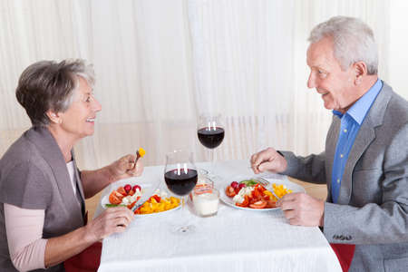 old people eating: Portrait Of Senior Couple With Wine Glasses Sitting At A Restaurant Stock Photo