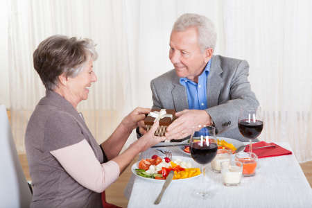 senior eating: Senior Man Giving Gift To Senior Woman In Restaurant