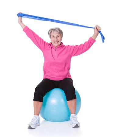 Senior Woman Stretching Exercising Equipment On White Background photo